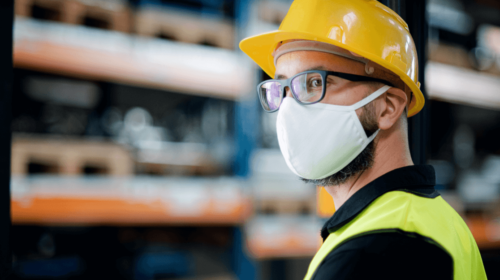 Close-up of a male worker wearing a yellow safety vest, helmet, goggles and mask
