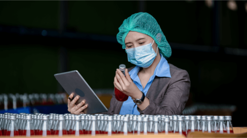 Woman holding a sample and tablet for blog How to get your OEE calculation right with a DMOS
