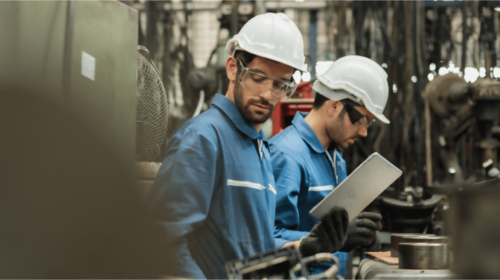 Two operators on the factory floor in overalls, one holding a tablet, both wearing goggles and helmets
