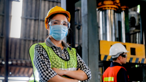 Female worker in a factory looking straight into the camera, crossed arms, wearing a safety vest, mask, goggles and helmet