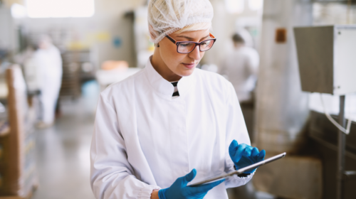 Female worker wearing lab coat, gloves and a tablet in food factory